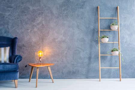 Intérieur avec fauteuil, lampe en cuivre, table d'appoint et support de fleurs Banque d'images
