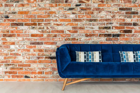 upholstered: Red brick wall and blue sofa with decorative pillows Stock Photo