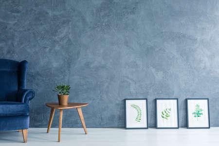 青い肘掛け椅子、サイド テーブルが付いているアパートと絵画の葉 写真素材 - 70237207