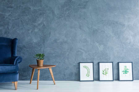 Apartment with blue armchair, side table and leaves paintings