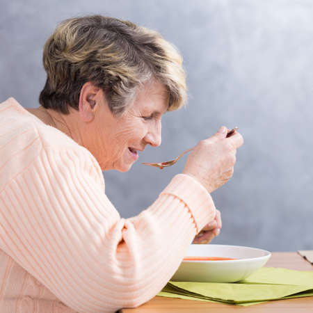Senior woman sitting beside table and eating a soup