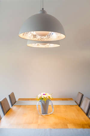 White room with wood dining table and ceiling lamp