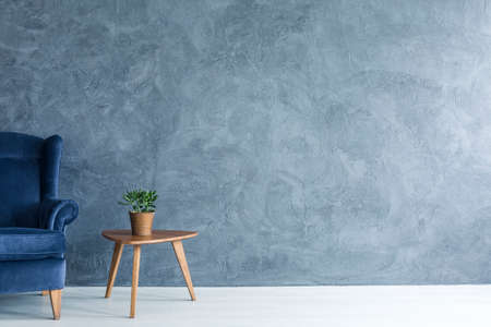 side table: Interior with grey wall blue armchair and wood side table Stock Photo