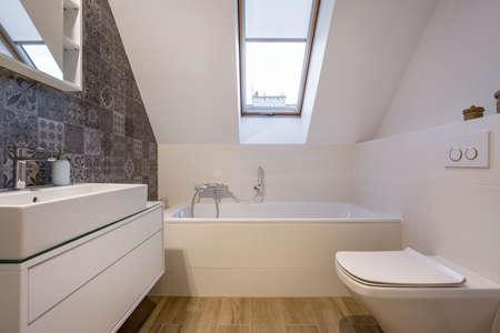 attic window: Attic bathroom with bathtub, window,, toilet and basin Stock Photo