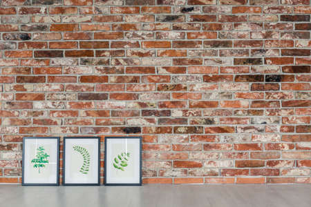 wall paintings: Red brick wall and decorative leaves paintings Stock Photo