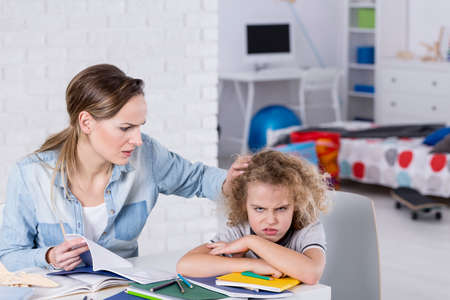 pouty: Pouty school doing homework with his worried mother Stock Photo