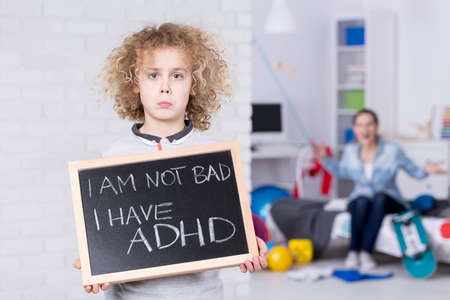 Sad ADHD boy holding small board, shouting mother in background Stock Photo