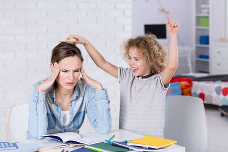 hyperactivity: Child annoying his tired mother with headache