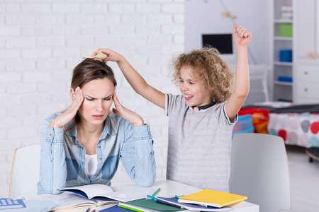 molesto: Niño molesta a su madre cansada con dolor de cabeza