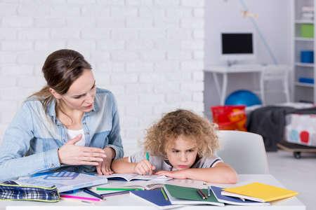 La madre y el niño que tiene un problema con la concentración, mientras que hacer la tarea