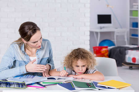Mother and child having problem with concentration while doing homework Stok Fotoğraf
