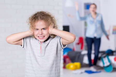 Misbehaving child covering his ears, mother shouting in background Stock Photo