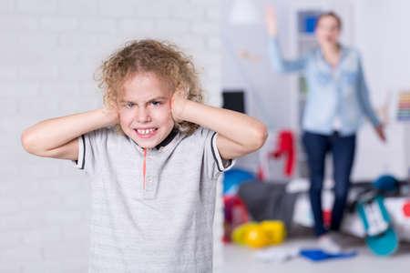 Misdragen kind die zijn oren, moeder schreeuwen in de achtergrond