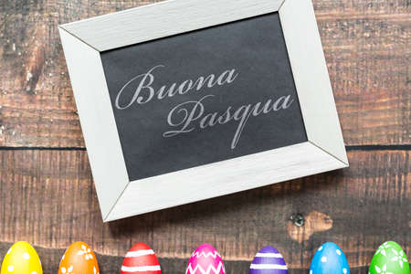 easter eggs: Decorative composition with easter eggs and blackboard on wood background Stock Photo