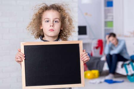 Droevige kindjongen die met krullend haar klein bord houden Stockfoto