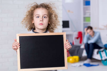 Sad child boy with curly hair holding small blackboard