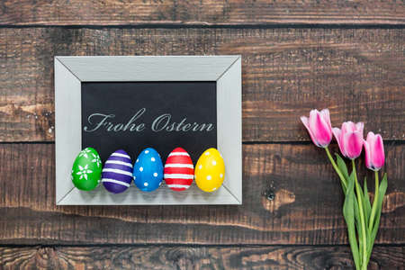 frohe: Composition with colorful easter eggs, small blackboard and pink tulips