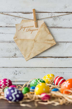 pascha: Card with easter eggs and decorative raffia on rustic table