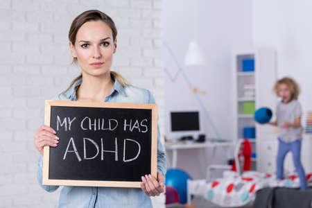 テキストの小さな黒板を保持している ADHD を持つ子の母 写真素材