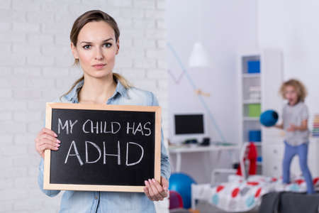Mother of child with ADHD holding small blackboard with text