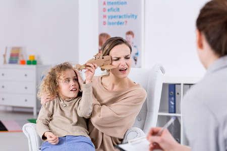 infancia: TDAH niño molesta a su madre en la oficina psicólogo Foto de archivo