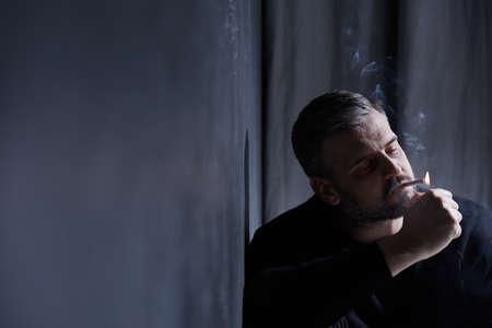 desolación: hombre roto para fumar que tiene depresión a causa de la separación