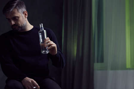 despondency: Man with alcohol addiction in gloomy room Stock Photo