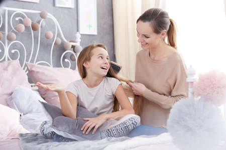 Happy woman brushing her daughters hair, sitting on bed