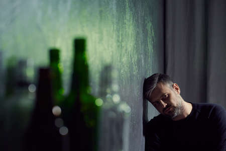 despondency: Man suffering from depression with empty alcohol bottles Stock Photo