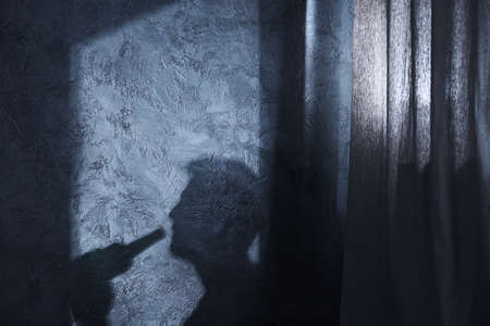Shadow of drinking man on the wall