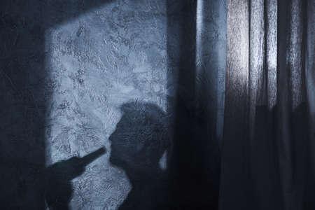 Schaduw van drinkende man aan de muur