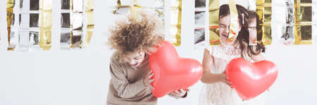 move in: Kids keeping red balloons in heart shape Stock Photo