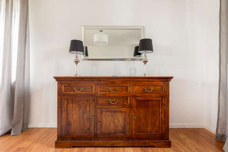 commode: Closer shot of stylish wooden commode with two lamps on it and the mirror above