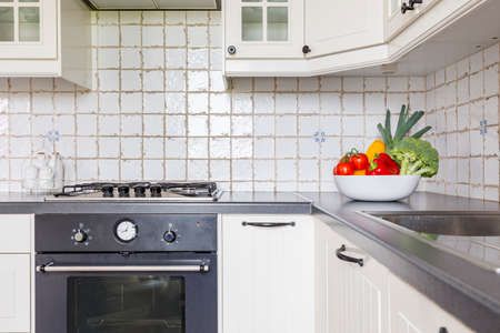 kitchen island: Bright kitchen with white units, stylish oven and bowl of vegetables on the worktop Stock Photo