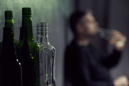 despondency: Empty bottles of alcohol with drinking man