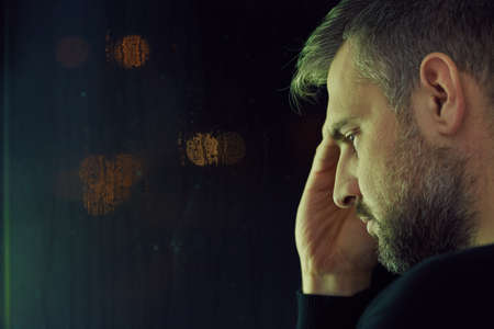 despondency: Thoughtful mature man with depression sitting alone Stock Photo