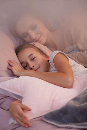 Happy girl sleeping in bed with her mother Stock Photo