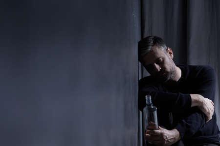 desolación: Man holding bottle of alcohol in dark interior Foto de archivo