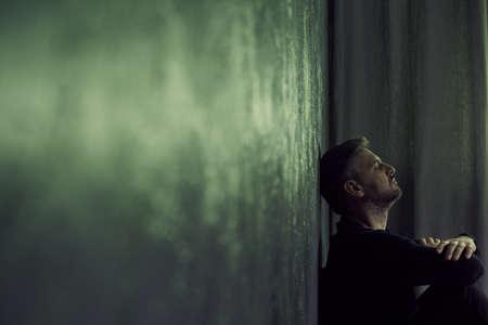 desolación: Deprimido hombre sentado solo en la habitación sombría