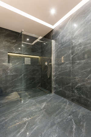 soaping: Very modern bathroom with grey tiles Stock Photo