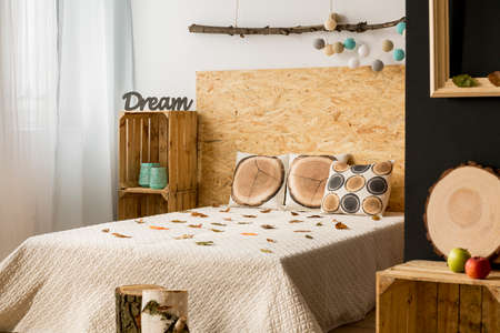 lightsome: Calm and lightsome studio apartment with double bed, wooden decoration and blackboard wall Stock Photo
