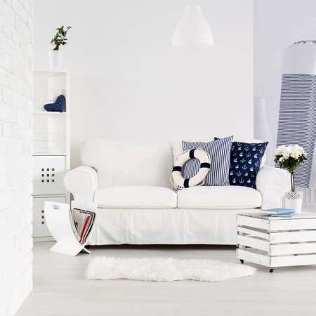 White spacious living room with brick wall, sofa and decorations in marine style