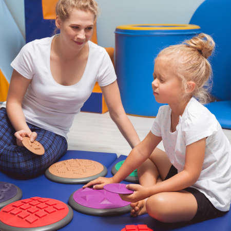 vestibular: Child touching with closed eyes sensory integration equipment with occupational therapist Stock Photo