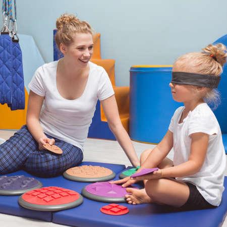 작업 치료사와 감각 통합 치료를하는 동안 눈가에 밴드가있는 아이