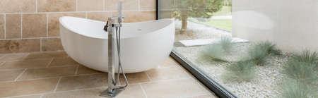 bathroom wall: Modern designed bathtub in a bathroom with glass wall