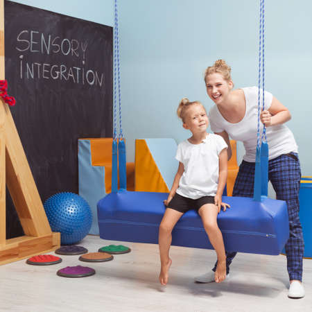 Sensory integration class for kid with female tutor at school gym