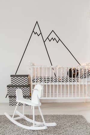 Well-lighted child room with crib and cockhorse