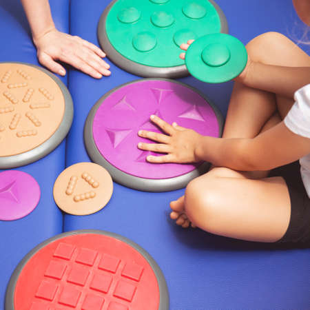 Child with occupational therapist touching sensory integration equipment Reklamní fotografie - 70963835