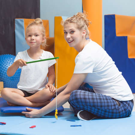 Sensory integration therapist helping child to keep balance during therapy