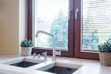 cosy: Kitchen window close to the wide tabletop with two sinks and flower pots on it Stock Photo